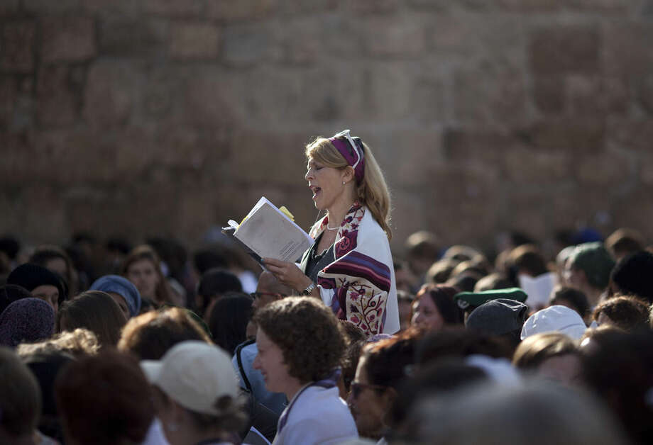 FILE - In this Monday, Nov. 4, 2013, file photo, a Jewish woman wears a prayer shawl as she prays at the Western Wall, the holiest site where Jews can pray in Jerusalem's Old City. Israeli Prime Minister Benjamin Netanyahu is advancing a plan to allow non-Orthodox Jewish prayer at the Western Wall in Jerusalem, a move advocates say would mark unprecedented government support for liberal streams of Judaism. According to the government proposal Israel would build a new plaza for mixed gender prayer at the Western Wall, adjacent to the Orthodox prayer plaza. (AP Photo/Ariel Schalit, File)