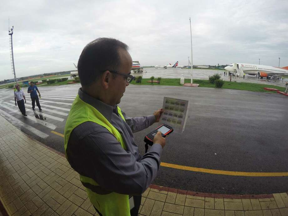 In this Thursday, June 9, 2016, photo, Galo Beltran, Cuba country manager for American Airlines, tests a handheld baggage scanner at Havana's Jose Marti International Airport. Beltran is based in Dallas. The Department of Transportation said Friday that six airlines: American, Frontier, JetBlue, Silver Airways, Southwest and Sun Country, have been selected for routes to nine Cuban cities other than Havana. (AP Photo/Scott Mayerowitz) Photo: Scott Mayerowitz / Associated Press / AP