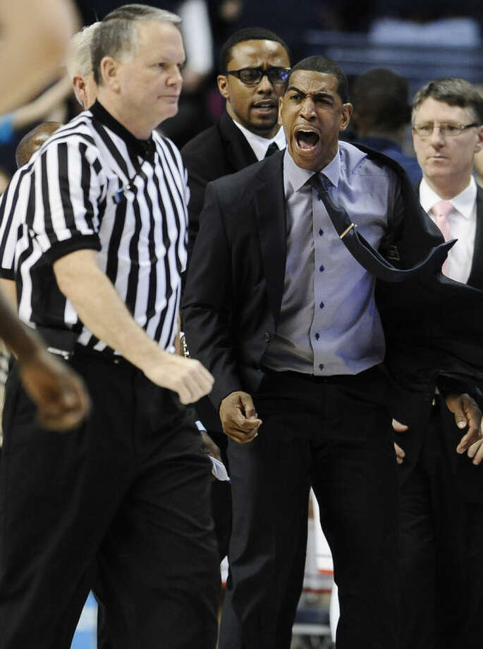 Connecticut head coach Kevin Ollie, right, yells toward an official during the second half of an NCAA college basketball game against Louisville, Saturday, Jan. 18, 2014, in Storrs, Conn. Ollie received two technical's and was ejected from the game. (AP Photo/Jessica Hill)