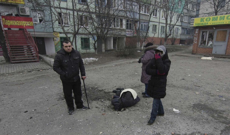 A dead body surrounded by local residents lays on the ground in a residential area in Mariupol, Ukraine, Saturday, Jan. 24, 2015. A crowded open-air market in Ukraine's strategically important coastal city of Mariupol came under rocket fire Saturday morning, killing at least 10 people, regional police said. Heavy fighting in the region in the autumn raised fears that Russian-backed separatist forces would try to establish a land link between Russia and Crimea. Pro-Russian separatist forces have positions within 10 kilometers (six miles) from Mariupol's eastern outskirts. (AP Photo/Sergey Vaganov)
