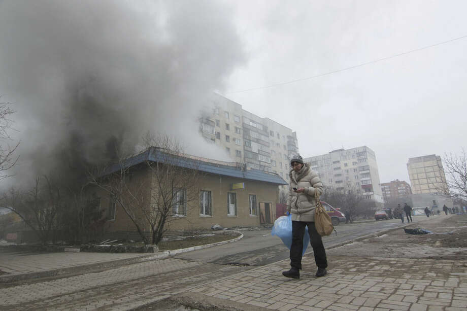 A woman resident passes by a burning house in Mariupol, Ukraine, Saturday, Jan. 24, 2015. A crowded open-air market in Ukraine's strategically important coastal city of Mariupol came under rocket fire Saturday morning, killing at least 10 people, regional police said. Heavy fighting in the region in the autumn raised fears that Russian-backed separatist forces would try to establish a land link between Russia and Crimea. Pro-Russian separatist forces have positions within 10 kilometers (six miles) from Mariupol's eastern outskirts. (AP Photo/Sergey Vaganov)