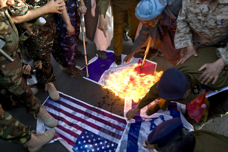 Yemeni protesters burn representations of French, American and Israeli flags during a demonstration to show their support for Houthi Shiite rebels in Sanaa, Yemen, Friday, Jan. 23, 2015. Thousands of protesters demonstrated Friday across Yemen, some supporting the Shiite rebels who seized the capital and others demanding the country's south secede after the nation's president and Cabinet resigned. (AP Photo/Hani Mohammed)