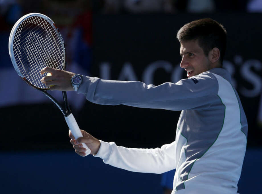 Serbia's Novak Djokovic impersonates his coach and former Grand Slam champion Boris Becker's service action following his fourth round win over Italy's Fabio Fognini at the Australian Open tennis championship in Melbourne, Australia, Sunday, Jan. 19, 2014. (AP Photo/Eugene Hoshiko)