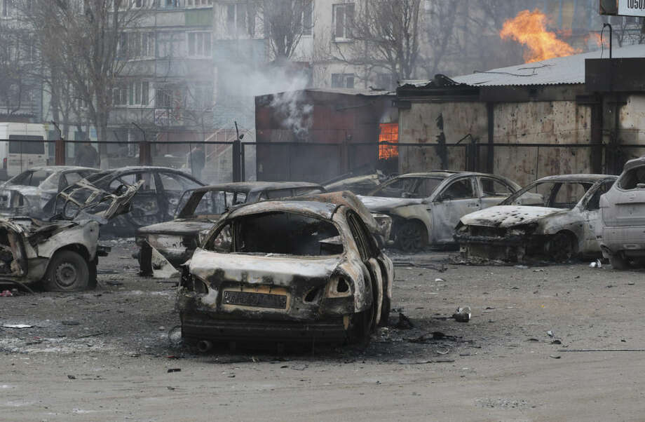 Burned cars on a destroyed parking site in a residential area in Mariupol, Ukraine, Saturday, Jan. 24, 2015. A crowded open-air market in Ukraine's strategically important coastal city of Mariupol came under rocket fire Saturday morning, killing at least 10 people, regional police said. Heavy fighting in the region in the autumn raised fears that Russian-backed separatist forces would try to establish a land link between Russia and Crimea. Pro-Russian separatist forces have positions within 10 kilometers (six miles) from Mariupol's eastern outskirts. (AP Photo/Sergey Vaganov)