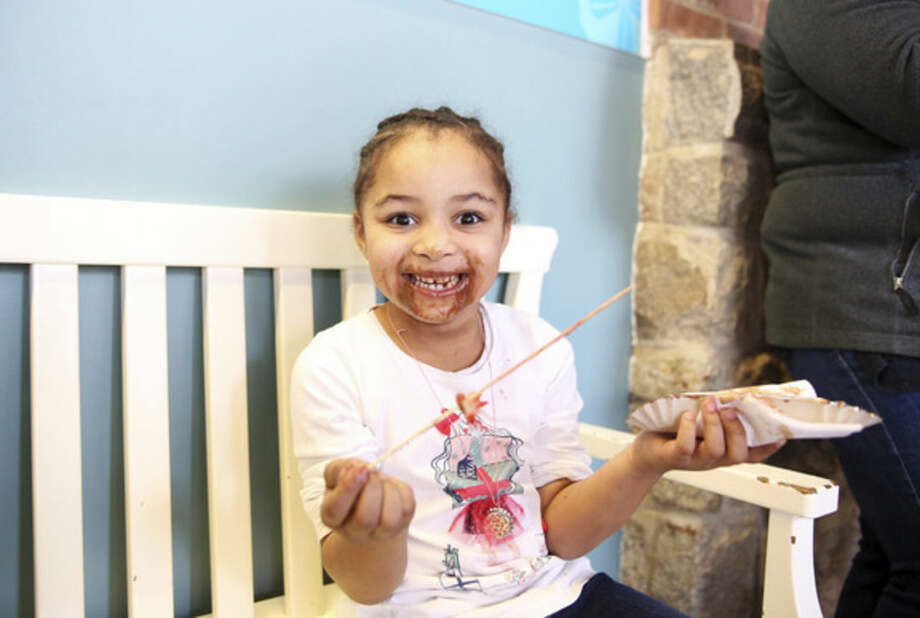 Briana Ruffin, 5, finishes her chocolate covered strawberries during the Chocolate Expo at the Maritime Aquarium in Norwalk Sunday morning.Hour Photo / Danielle Calloway