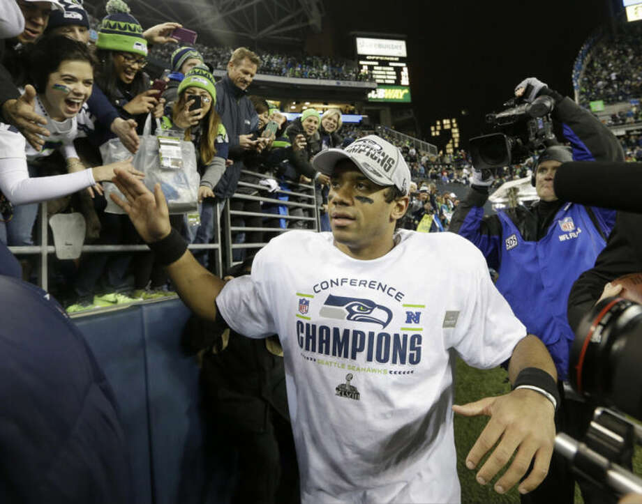 Seattle Seahawks' Russell Wilson celebrates with fans after the NFL football NFC Championship game against the San Francisco 49ers, Sunday, Jan. 19, 2014, in Seattle. The Seahawks won 23-17 to advance to Super Bowl XLVIII. (AP Photo/Elaine Thompson)