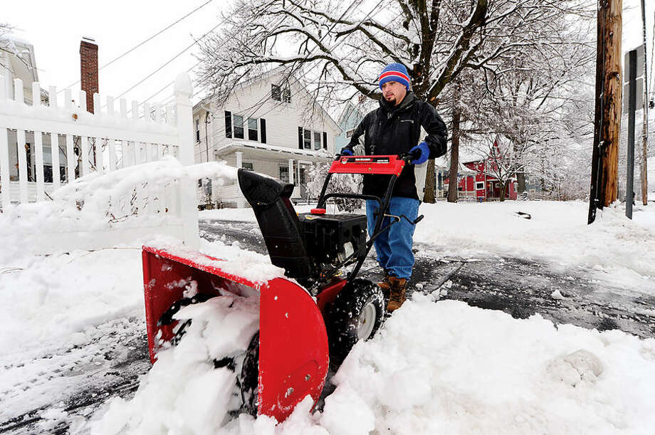 Hour photo / Erik Trautmann Antonio Migliaccio clears sidewalks outside his home on St. John St following the 4 inches of wet snow that blanketed Norwalk early Saturday morning.