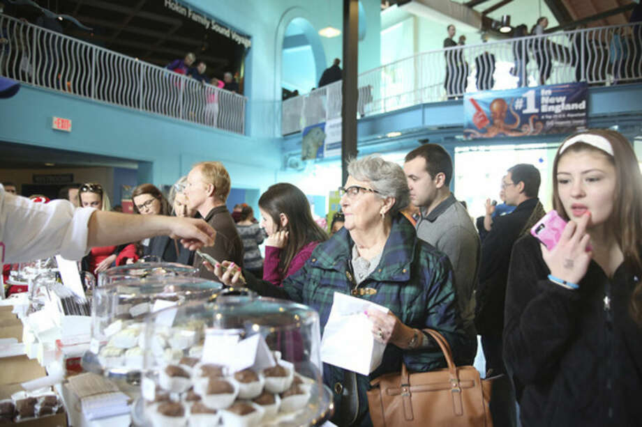Hour photos/Danielle CallowayClarisse Morrisey buys some chocolate from The Village Chocolate Shoppe during the Chocolate Expo at the Maritime Aquarium in Norwalk Sunday morning.