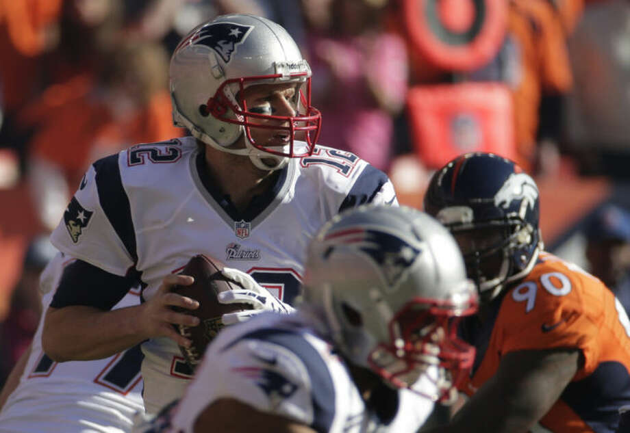 New England Patriots quarterback Tom Brady (12) looks for an opening to pass during the first half of the AFC Championship NFL playoff football game against the Denver Broncos in Denver, Sunday, Jan. 19, 2014. (AP Photo/Charlie Riedel)