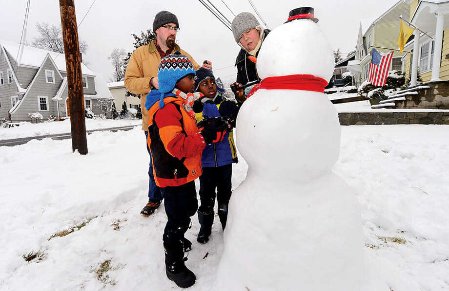 Hour photo / Erik Trautmann Mark and Heidi Newcomb and their sons Taye and Dash, 7, build a snowman outside their home on Raymond Terrace following the 4 inches of wet snow that blanketed Norwalk early Saturday morning.