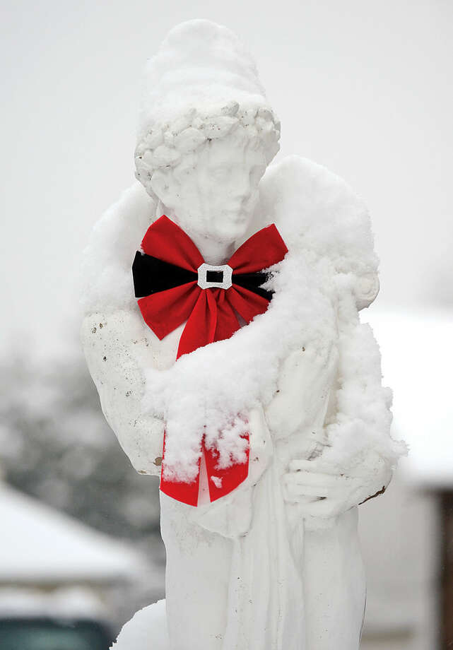 Hour photo / Erik Trautmann A statue is covered with snow along Osbourne Ave following the 4 inches of wet snow blanketed Norwalk early Saturday morning.
