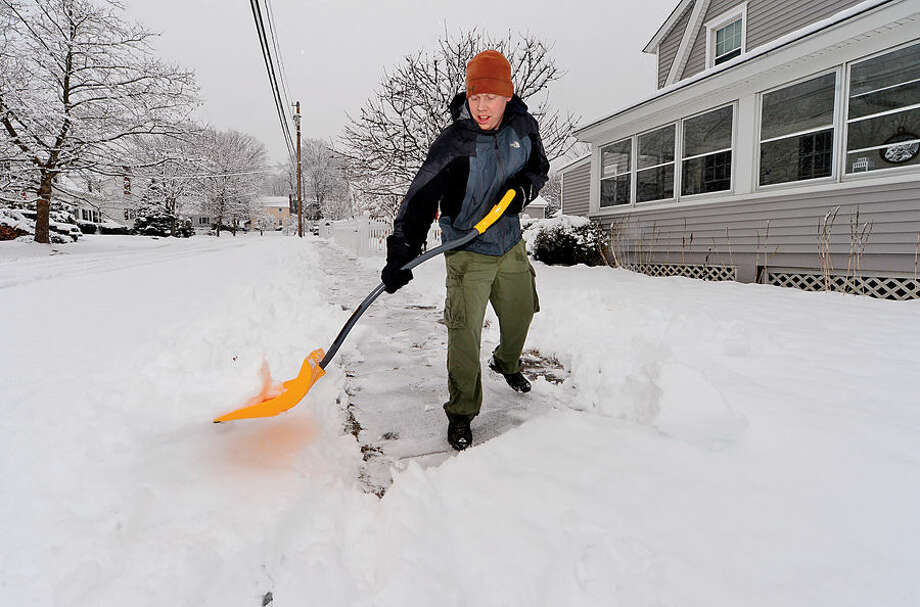 Hour photo / Erik Trautmann Ryan McMurrer shovels the sidewalk outside of his home on Ludlowe and Gregory following the 4 inches of wet snow that blanketed Norwalk early Saturday morning.
