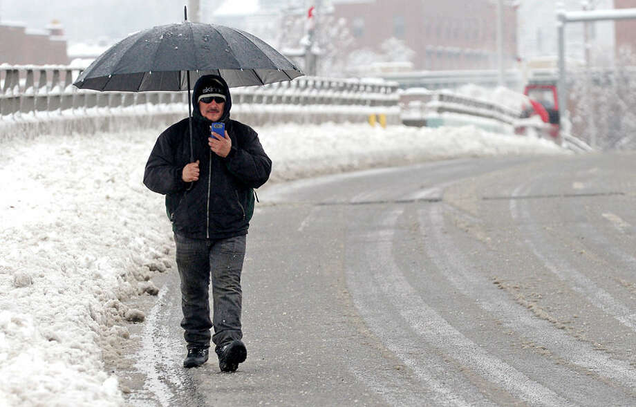 Hour photo / Erik Trautmann Rico Martinez walks to work in the roadway following the 4 inches of wet snow that blanketed Norwalk early Saturday morning.