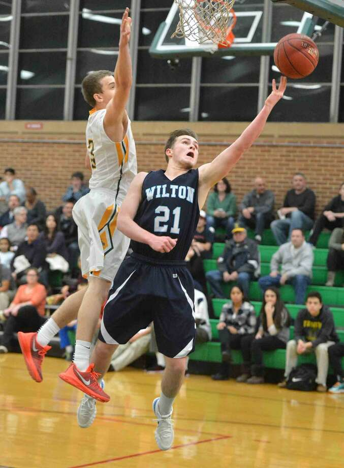 Wilton's No. 21 John Williams shoots vs Trinity Catholic.