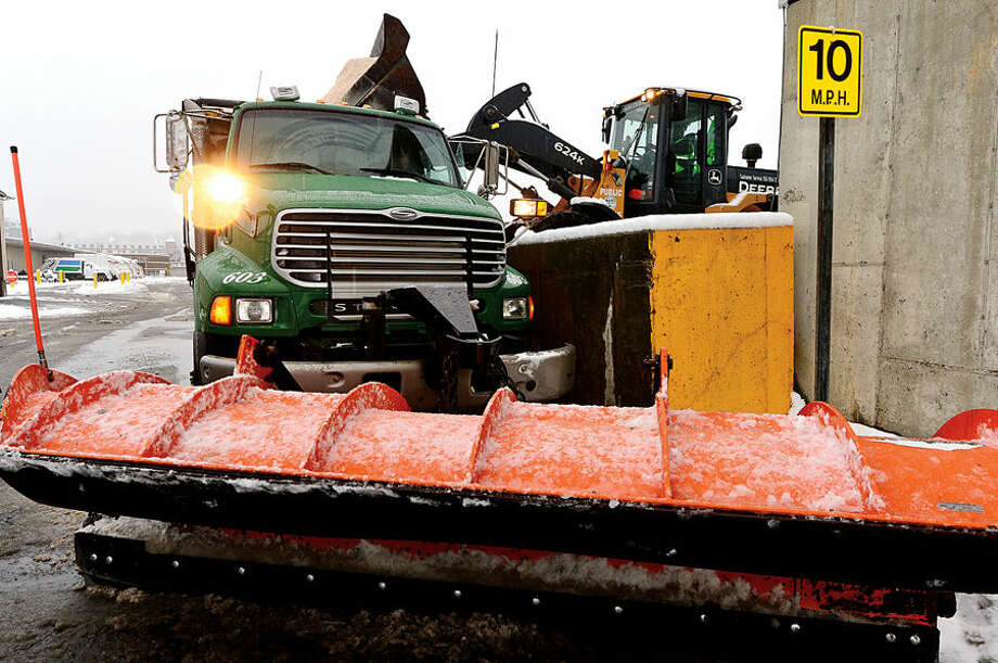 Hour photo / Erik Trautmann A Norwalk Department of Public Works plow truck is filled with a sand salt mixture following the 4 inches of wet snow that blanketed Norwalk early Saturday morning.