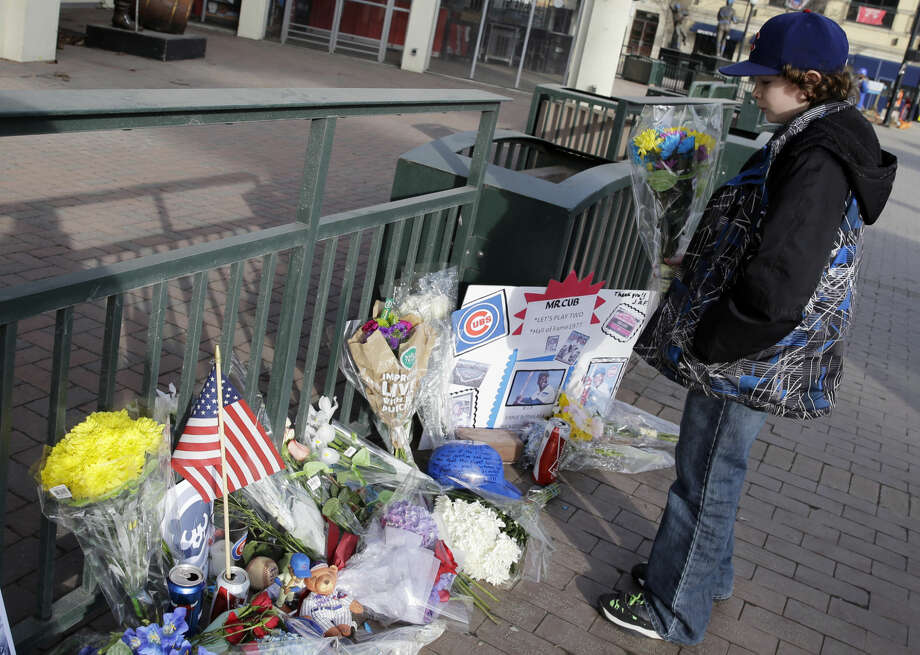 Noah Delfosse, 11, from Arlington heights, Ill., stands among flowers outside Wrigley Field in remembrance of Cubs baseball legend Ernie Banks in Chicago, Saturday, Jan. 24, 2014. Banks died at the age of 83. 'Mr. Cub' passed away Friday night at Northwestern Memorial Hospital in Chicago. (AP Photo/Nam Y. Huh)
