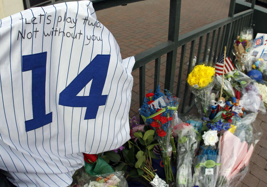 Fans left a jersey, flowers, candles and a hat in front of Wrigley Field in honor of Cub's baseball legend Ernie Banks in Chicago, Saturday, Jan. 24, 2014. Chicago Cubs legend Ernie Banks has died at the age of 83. 'Mr. Cubs' passed away Friday night at Northwestern Memorial Hospital in Chicago.(AP Photo/Nam Y. Huh)