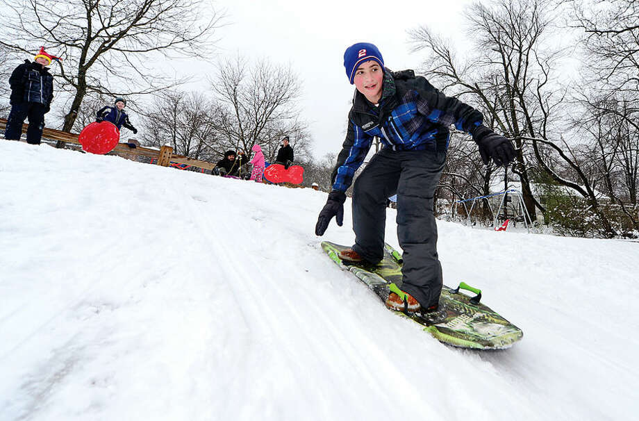 Hour photo / Erik Trautmann Graham Resnick, 12, sleds at Wolfpit School following the snowfall early Saturday morning.
