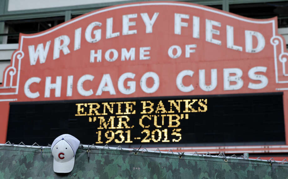 A Chicago Cubs hat hangs on the construction fence in front of Wrigley Field in honor of Ernie Banks in Chicago, Saturday, Jan. 24, 2014. Chicago Cubs legend Ernie Banks has died at the age of 83. 'Mr. Cub' passed away Friday night at Northwestern Memorial Hospital in Chicago.(AP Photo/Nam Y. Huh)