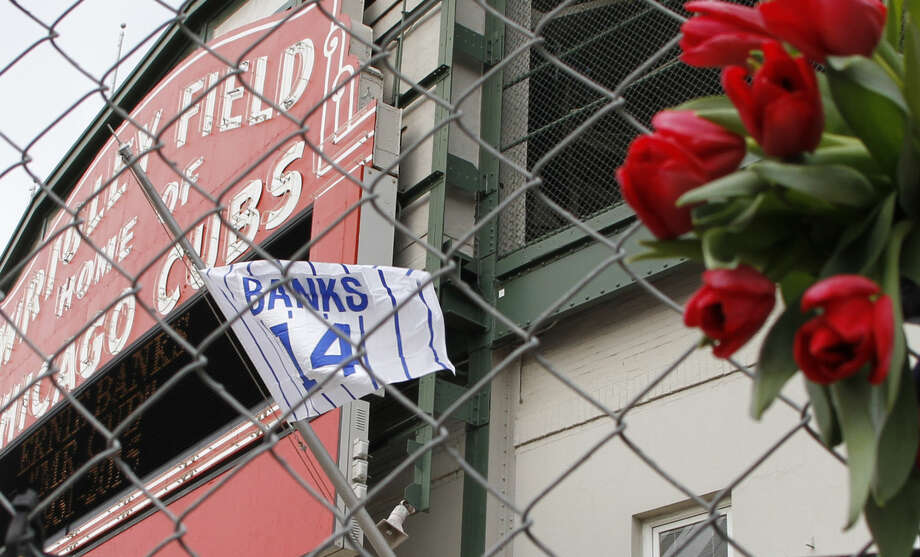 Flowers hang on the construction fence in front of Wrigley Field in honor of Ernie Banks in Chicago, Saturday, Jan. 24, 2014. Banks died at the age of 83. 'Mr. Cub' passed away Friday night at Northwestern Memorial Hospital in Chicago.(AP Photo/Nam Y. Huh)