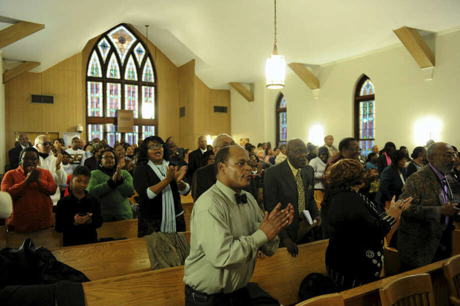 People stand to the feet during the music portion of the Black History Committee's celebration of Dr. Martin Luther King, Jr's birthday at Greater Norris Chapel Baptist Church in Henderson, Ky Sunday Jan. 19, 2014. (AP Photo/The Gleaner, Darrin Phegley)