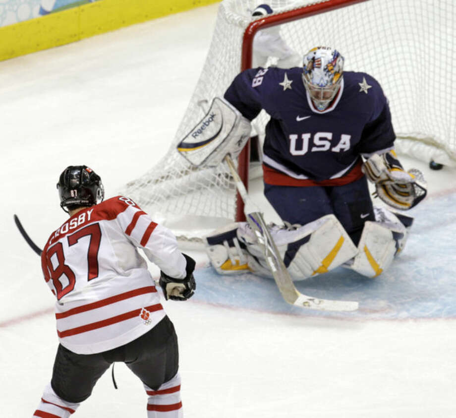 FGILE - In a Feb. 28, 2010 file photo Canada's Sidney Crosby (87) shoots past USA goalie Ryan Miller (39) for the game-winning goal in the overtime period of a men's gold medal ice hockey game at the Vancouver 2010 Olympics in Vancouver, British Columbia. Crosby will captain the Canadian hockey team at the Olympics in Sochi. (AP Photo/Chris O'Meara, file)