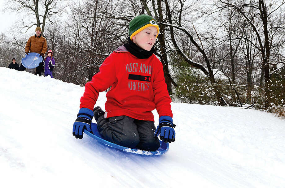 Hour photo / Erik Trautmann Seamus Herlihy, 10, sleds at Wolfpit School following the snowfall early Saturday morning.
