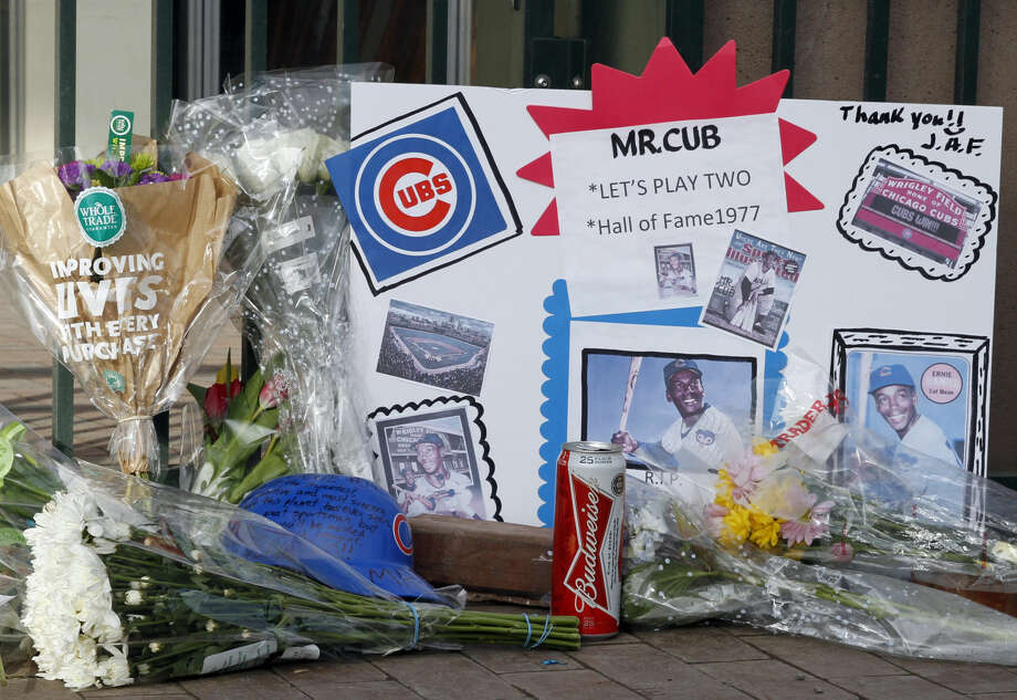 Fans left flowers, candles and a hat in front of Wrigley Field in honor of Cub's baseball legend Ernie Banks in Chicago, Saturday, Jan. 24, 2014. Banks died at the age of 83, Friday night at Northwestern Memorial Hospital in Chicago.(AP Photo/Nam Y. Huh)