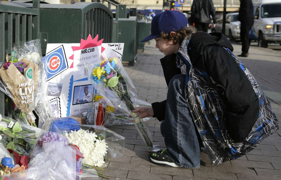 Noah Delfosse, 11, from Arlington heights, Ill., lays flowers outside Wrigley Field in remembrance of Cubs baseball legend Ernie Banks in Chicago, Saturday, Jan. 24, 2014. Chicago Cubs legend Ernie Banks has died at the age of 83. 'Mr. Cubs' passed away Friday night at Northwestern Memorial Hospital in Chicago. (AP Photo/Nam Y. Huh)