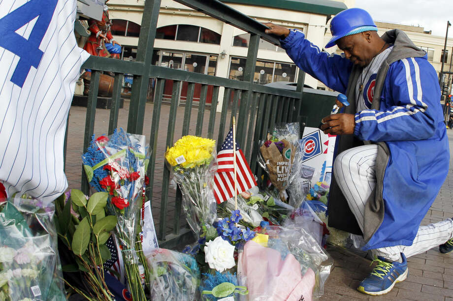 Ronnie Wickers (WooWoo) lays a doll outside Wrigley Field in remembrance of Cubs baseball legend Ernie Banks in Chicago, Saturday, Jan. 24, 2014. Banks died at the age of 83, Friday night at Northwestern Memorial Hospital in Chicago. (AP Photo/Nam Y. Huh)