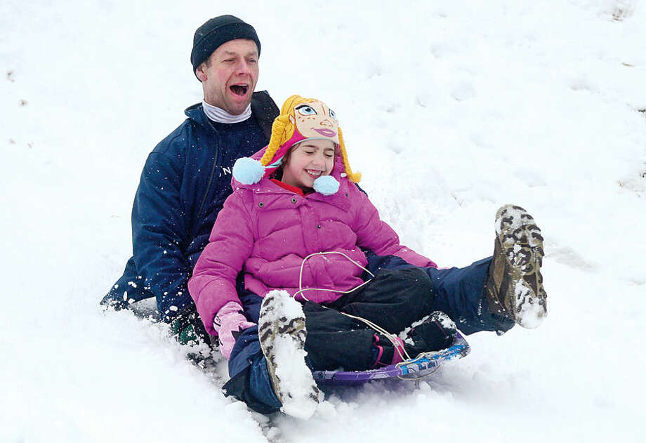 Hour photo / Erik Trautmann Tom Lampman and his daughter Ava, 7, sled at Wolfpit School following the snowfall early Saturday morning.