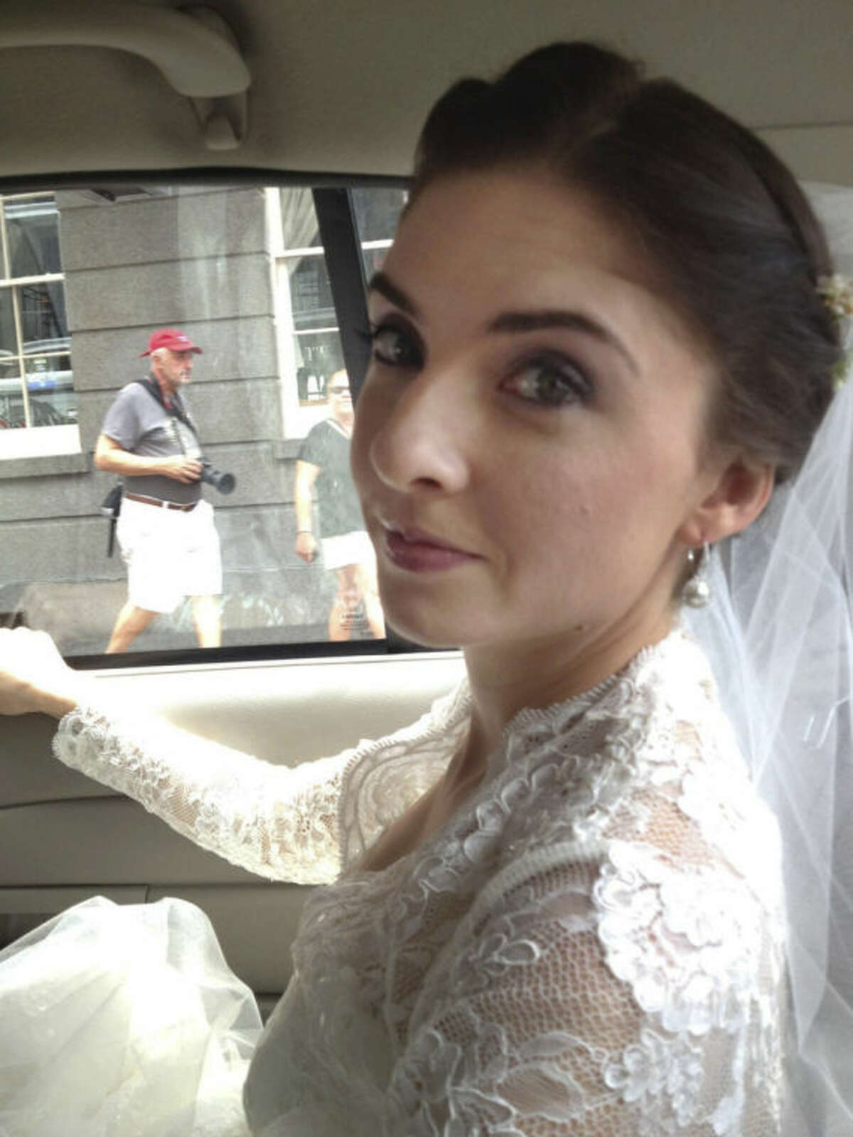 This Oct. 12, 2013 photo provided by Cheryl Winter shows her daughter, Shannon, riding in a taxi to her wedding in New Orleans, after her limousine failed to arrive. Cheryl Winter spent $500 for Hartford-based Travelers Insurance to cover Shannon?'s destination wedding, where her biggest concern was a potential hurricane. The weather cooperated, but after the limo failed to show, they used the insurance policy to claim the deposit money they could not get back from the driver. (AP Photo/Nora Peach)