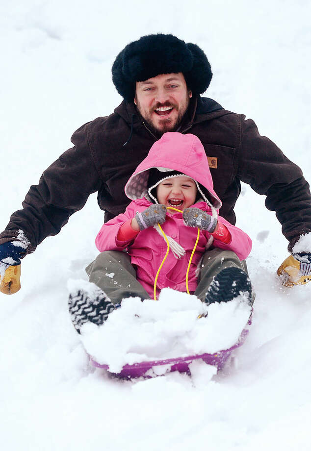 Hour photo / Erik Trautmann Rob Flemming and Julia Cleary, 3, sled at Wolfpit School following the snowfall early Saturday morning.