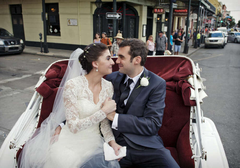 This Oct. 12, 2013 photo provided by Julia Bailey shows Shannon and Justin Peach, riding in a carriage after their wedding in New Orleans. Shannon's mom, Cheryl Winter, spent $500 for Hartford-based Travelers Insurance to cover her daughter's destination wedding, where her biggest concern was a potential hurricane. The weather cooperated, but after the limousine failed to show they used the insurance policy to claim the deposit money they could not get back from the limo driver. (AP Photo/Julia Bailey)