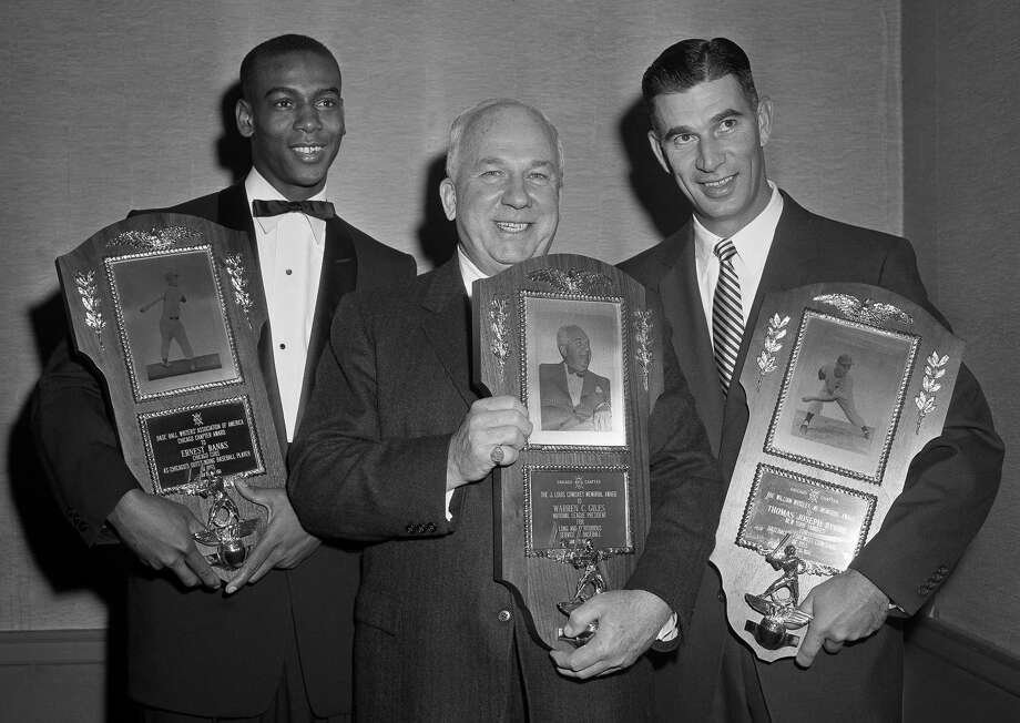 FILE - In this Jan. 15, 1956, file photo, three baseball men honored by Chicago baseball writers at their annual dinner display the plaques awarded them in Chicago. From left to right: Chicago Cubs' Ernie Banks, chosen Chicago's outstanding player; Warren Giles, National League president, honored for long and meritorious service to the game; and Tommy Byrne, New York Yankee pitcher, for baseball's finest comeback of 1955. The Cubs announced Friday night, Jan. 23, 2015, that Banks had died. The team did not provide any further details. Banks was 83. (AP Photo/File)