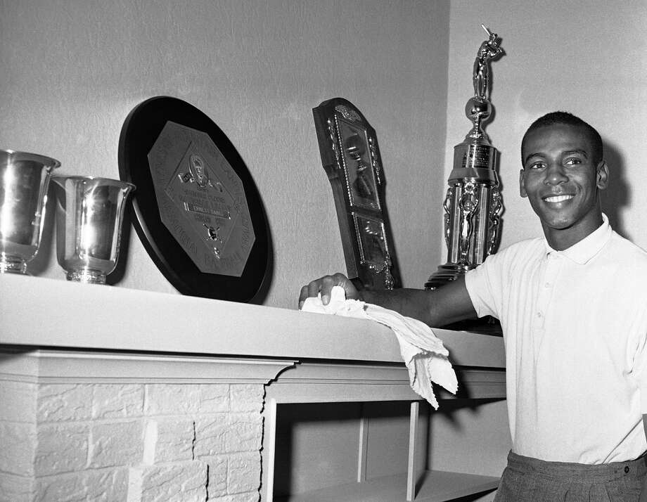 FILE - In this Nov. 5, 1959, file photo, Chicago Cubs shortstop Ernie Banks, who won the National League most valuable player award for the second successive year, makes room on his mantle for a new trophy in Chicago. The round plaque in center is the 1958 Most Valuable player award. The Cubs announced Friday night, Jan. 23, 2015, that Banks had died. The team did not provide any further details. Banks was 83. (AP Photo/CEK, File)