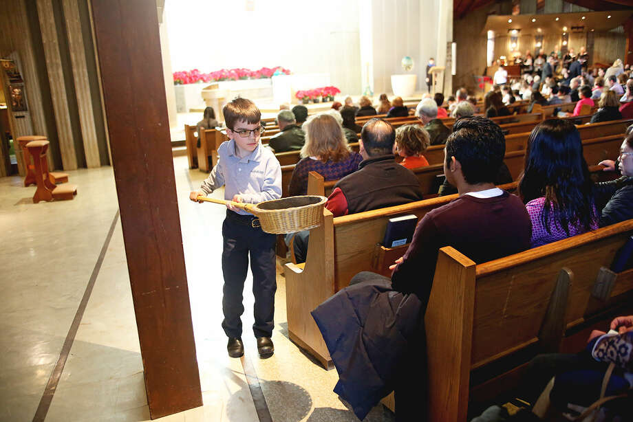 Anthony Szarpa, 8, collects donations during a Mass to kick off National Catholic Schools Week at St. Philips Parish in Norwalk Sunday morning. Hour Photo / Danielle Calloway