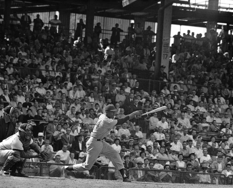 FILE - In this Aug. 31, 1955, file photo, Chicago Cubs' Ernie Banks, center, demonstrates the long stride and wrist action which has brought him close to the leaders in the National League home run race at Ebbets Field in New York. The Cubs announced Friday night, Jan. 23, 2015, that Banks had died. The team did not provide any further details. Banks was 83. (AP Photo/File)