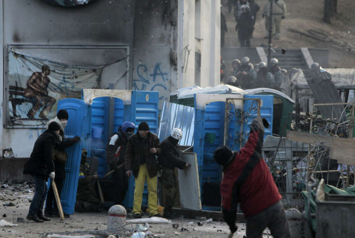 Protesters clash with police in central Kiev, Ukraine, Monday, Jan. 20, 2014. Protesters erected barricades in Kiev as the sound of stun grenades pierce the freezing air, after a night of rioting and street protests. (AP Photo/Sergei Chuzavkov)