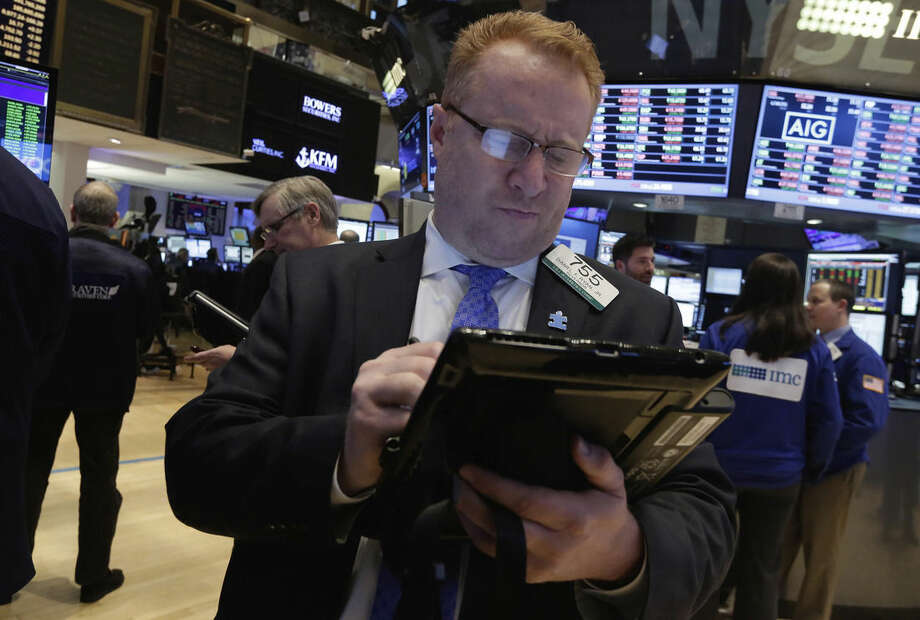 Trader Daniel Ryan works on the floor of the New York Stock Exchange Friday, Jan. 23, 2015. The stock market finished lower, snapping a four-day winning streak, as U.S. companies report mixed quarterly results. The Dow Jones industrial average dropped 141 points, or 0.8 percent, to 17,672. (AP Photo/Richard Drew)