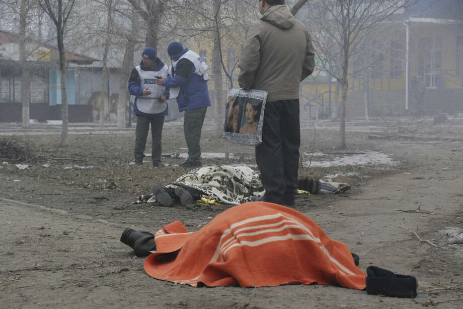 Two dead bodies lay on the ground in a residential area in Mariupol, Ukraine, OSCE members in the background, Saturday, Jan. 24, 2015. A crowded open-air market in Ukraine's strategically important coastal city of Mariupol came under rocket fire Saturday morning, killing at least 10 people, regional police said. Heavy fighting in the region in the autumn raised fears that Russian-backed separatist forces would try to establish a land link between Russia and Crimea. Pro-Russian separatist forces have positions within 10 kilometers (six miles) from Mariupol's eastern outskirts. (AP Photo/Sergey Vaganov)