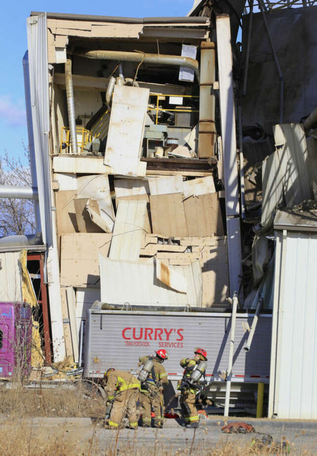 Firefighter stage outside the International Nutrition plant in Omaha, Neb., Monday, where a fire and explosion took place Jan. 20, 2014. At least nine people have been hospitalized and others could be trapped at the animal feed processing plant. (AP Photo/Nati Harnik)