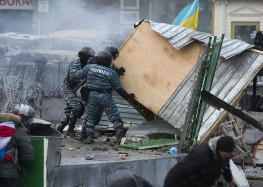 Police work to clear a barricade during unrest in central Kiev, Ukraine, Monday, Jan. 20, 2014. Protesters erected barricades from charred vehicles and other materials in central Kiev as the sound of stun grenades could be heard in the freezing air. (AP Photo/Sergei Chuzavkov)