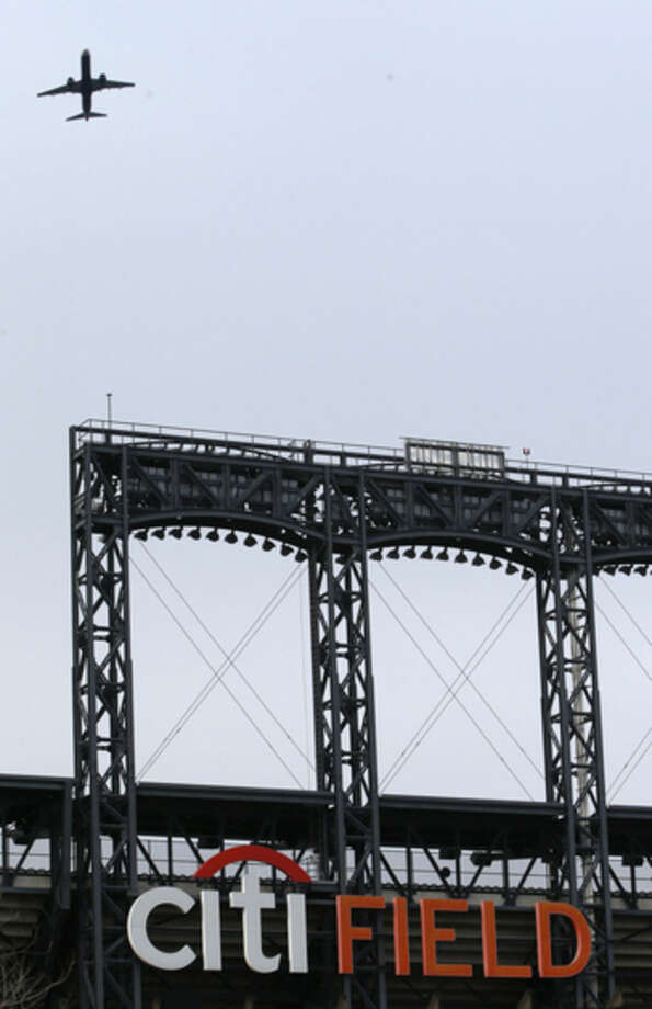 An airplane takes off from LaGuardia Airport passing over Citi Field, home to the New York Mets baseball team, in New York, Wednesday, Jan. 21, 2015. New York Gov. Andrew Cuomo has proposed a rail link to LaGuardia, one of the nations' busiest airports. Cuomo's plan calls for an elevated AirTrain connecting the airport with the Willets Point station, 1.5 miles away. The station serves both the Long Island Rail Road commuter rail and the No. 7 subway line. (AP Photo/Kathy Willens)