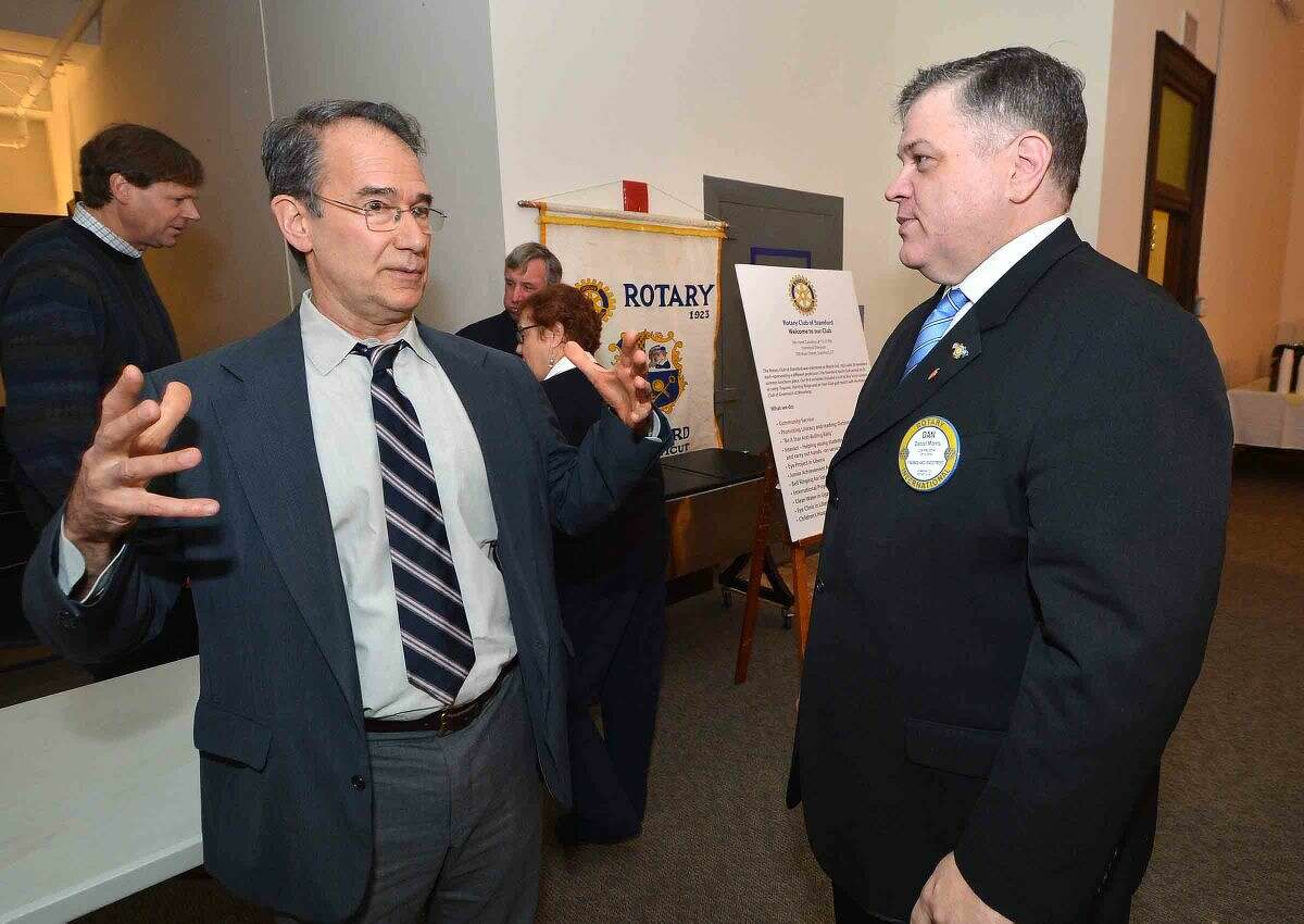 Dan Morris, president of The Rotary Club of Stamford, talks with guest speaker Chris George during a reception before he speaks about his role as executive director of Integrated Refugee & Immigrant Services at a Rotary Clubs of Lower Fairfield County Community Conversation.
