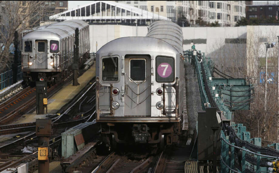 A No. 7 subway train arrives at the Mets-Willets point station, left, as another leaves the station in New York, Wednesday, Jan. 21, 2015. Gov. Andrew Cuomo has proposed a rail link to LaGuardia Airport, one of the busiest airports in the nation. Cuomo's plan calls for an elevated AirTrain connecting the airport with the Willets Point station 1.5 miles away. The station, opposite the Mets' ballpark, serves both the Long Island Rail Road commuter rail and the No. 7 subway line. (AP Photo/Kathy Willens)