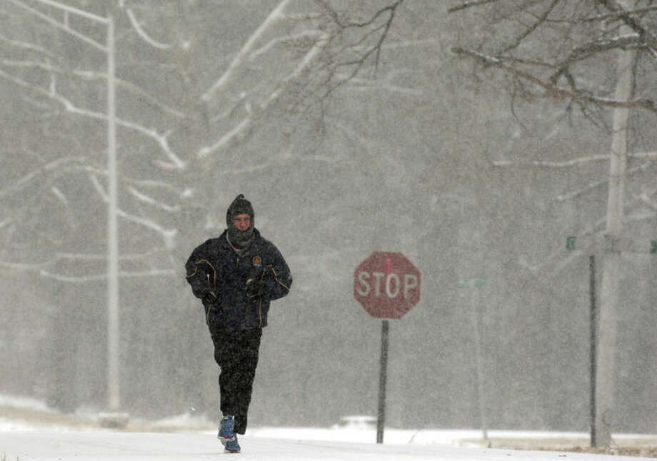 Greg Spadavecchia jogs as snow starts to fall in Morris Plains, N.J. on Tuesday, Jan. 21, 2014. A storm is expected to hit the northern New Jersey region throughout the day. Because of hazardous driving conditions New Jersey Gov. Chris Christie's inauguration party at Ellis Island was cancelled. (AP Photo/The Daily Record, Bob Karp ) NO SALES