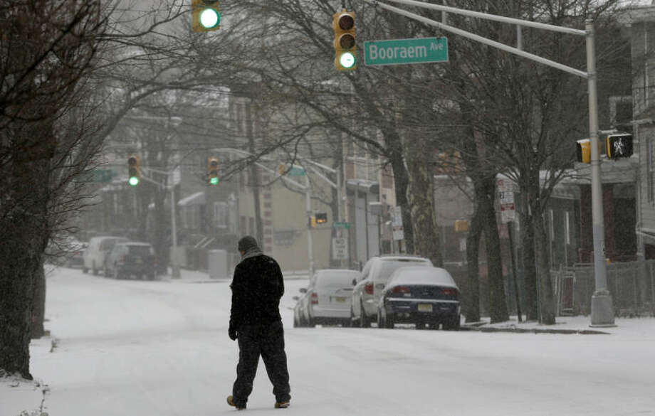 A man walks on a snow covered street, Tuesday, Jan. 21, 2014, in Jersey City, N.J. A storm is expected to hit the northern New Jersey region throughout the day. Because of hazardous driving conditions New Jersey Gov. Chris Christie's inauguration party at Ellis Island was cancelled. (AP Photo/Julio Cortez)