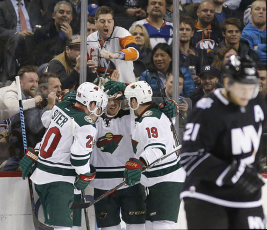 Minnesota Wild players celebrate with right wing Jason Pominville, center, after he scored during the second period of an NHL hockey game against the New York Islanders in New York, Tuesday, Feb. 2, 2016. (AP Photo/Kathy Willens)