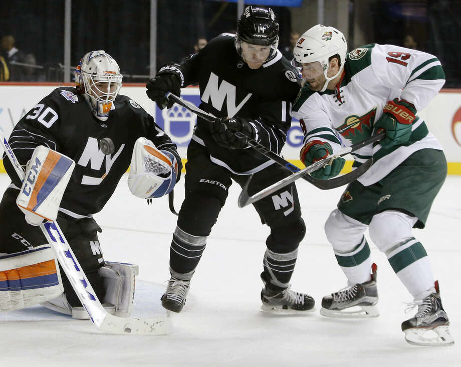 New York Islanders goalie Jean-Francois Berube (30) makes a save asslanders defenseman Thomas Hickey (14) defends Minnesota Wild center Jarret Stoll (19) during the first period of an NHL hockey game in New York, Tuesday, Feb. 2, 2016. (AP Photo/Kathy Willens)